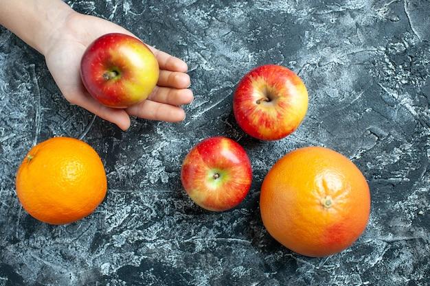 Vue de dessus pomme mûre dans les oranges et les pommes de la main féminine sur fond gris