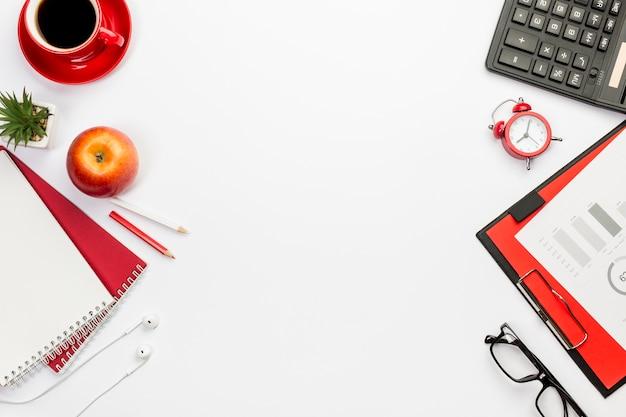 Une vue de dessus de pomme avec des papeteries sur un bureau blanc