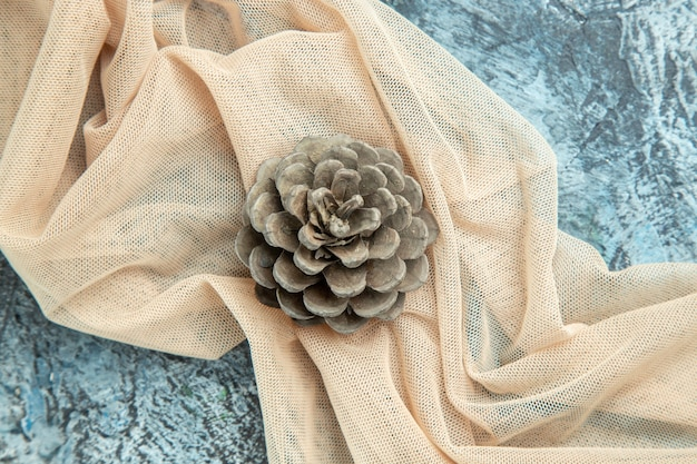 Vue De Dessus Pomme De Pin Sur Châle Beige Sur Surface Sombre Photo gratuit