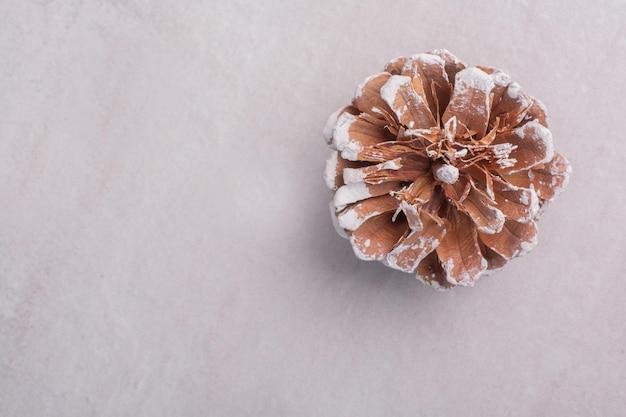 Vue de dessus de la pomme de pin sur une surface blanche.