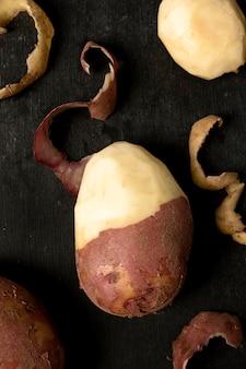 Vue de dessus de la pomme de terre à moitié pelée