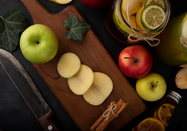 Vue de dessus de pomme verte en tranches avec des feuilles de lierre cannelle sur une planche de thé au citron pommes rouges et vertes