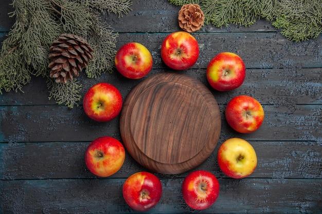 Vue de dessus des pommes autour de la planche neuf pommes sont disposées en cercle autour de la planche à découper entre les branches des arbres avec des cônes