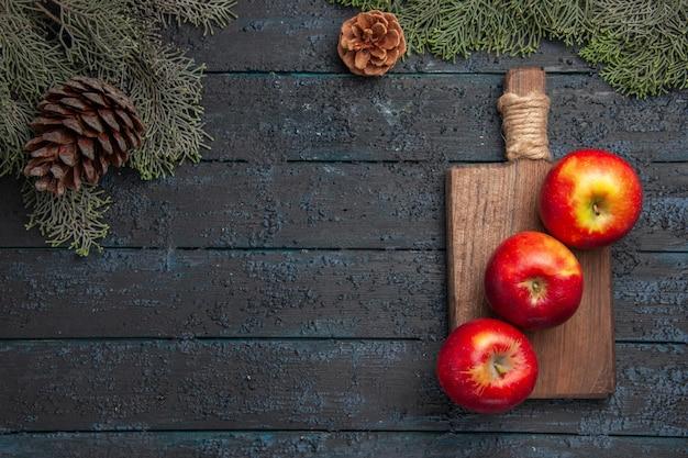 Vue de dessus des pommes à bord de trois pommes sur une planche à découper en bois sous des branches avec des cônes