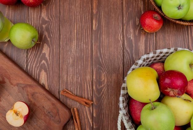 Vue de dessus des pommes dans des paniers et sur une planche à découper avec du jus de pomme cannelle sur fond de bois