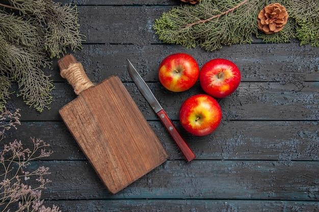 Vue de dessus des pommes et du couteau trois pommes jaune-rougeâtre à côté de la planche à découper en bois et du couteau sous les arbres avec des cônes