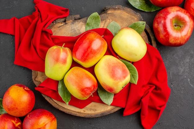 Vue de dessus des pommes fraîches aux pêches sur une table gris foncé couleur de fruits mûrs frais