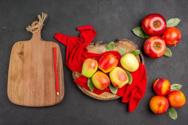 Vue de dessus des pommes fraîches aux pêches sur une table gris foncé fruits frais mûrs