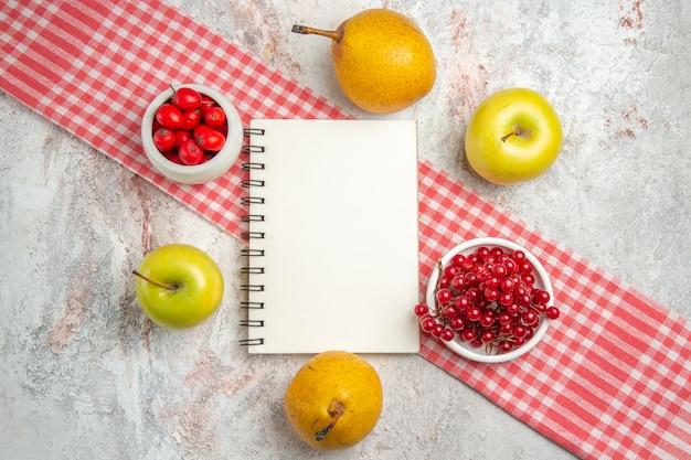 Vue de dessus des pommes fraîches avec des baies rouges et des poires sur la santé des arbres de baies de fruits de table blanche