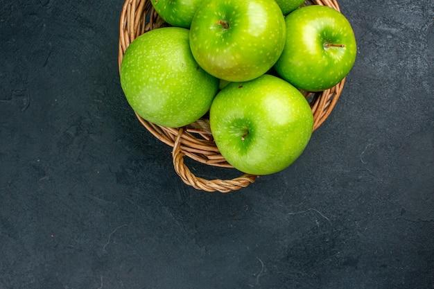 Vue de dessus des pommes fraîches dans un panier en osier sur une surface sombre