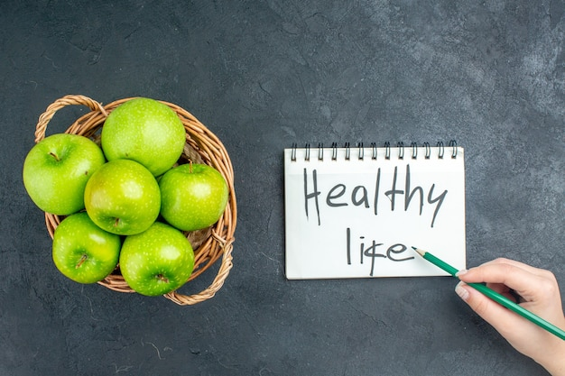 Vue de dessus des pommes fraîches dans le panier en osier vie saine écrite sur le crayon bloc-notes dans la main de la femme sur une surface sombre