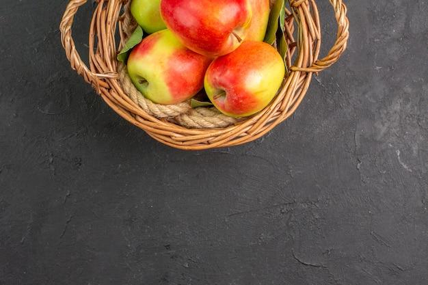 Vue de dessus pommes fraîches fruits mûrs à l'intérieur du panier sur table grise fruits frais mûrs