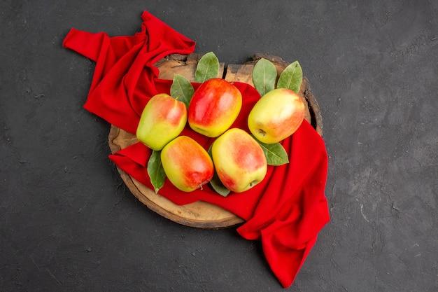 Vue de dessus pommes fraîches fruits mûrs sur tissu rouge et table grise fruits mûrs frais