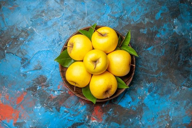 Vue de dessus des pommes fraîches à l'intérieur de la plaque sur fond bleu couleur de régime de santé mûr et moelleux