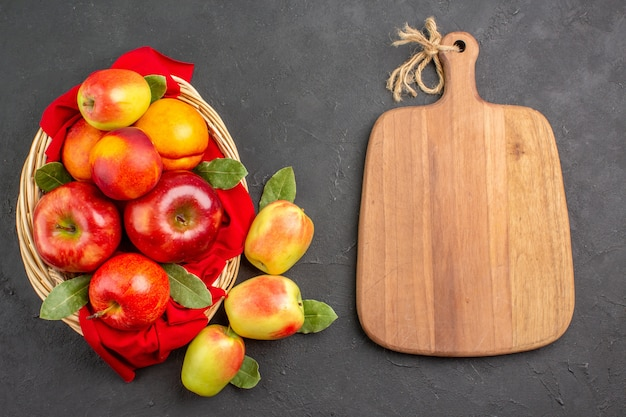 Vue de dessus des pommes fraîches avec des pêches à l'intérieur du panier sur des fruits de table gris foncé mûrs frais