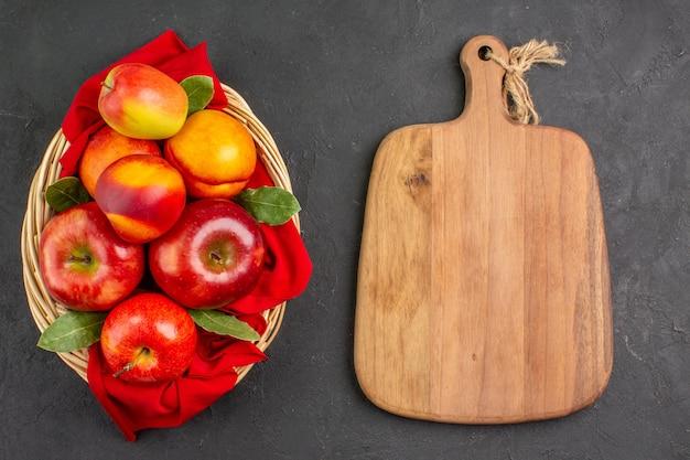 Vue de dessus des pommes fraîches avec des pêches à l'intérieur du panier sur une table sombre arbre fruitier frais mûr
