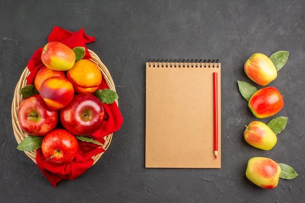 Vue de dessus des pommes fraîches avec des pêches à l'intérieur du panier sur la table sombre des fruits frais mûrs
