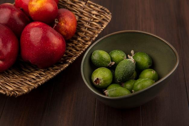 Vue de dessus des pommes fraîches sur un plateau en osier avec feijoas sur un bol sur un mur en bois