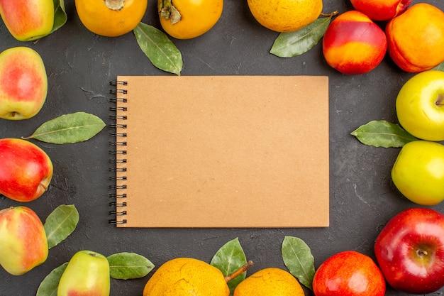 Vue de dessus des pommes fraîches avec des poires et des kakis sur l'arbre de la table sombre moelleux frais mûrs