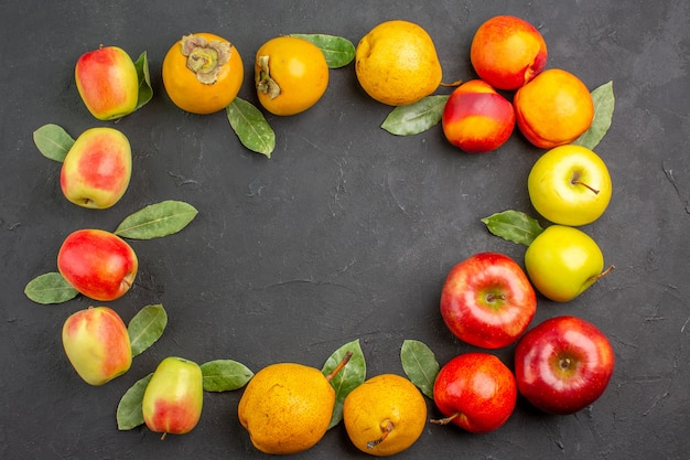Vue de dessus des pommes fraîches avec des poires et des kakis sur la table sombre arbre frais mûr et mûr