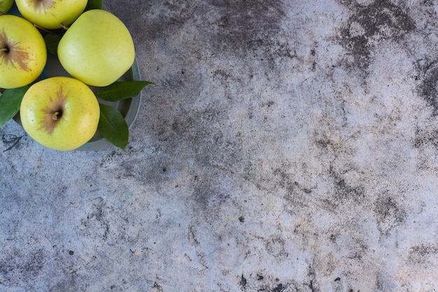 Vue de dessus des pommes fraîches vertes avec des feuilles sur fond gris.