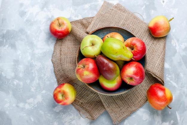 Vue de dessus des pommes de fruits frais et de la mangue sur une surface blanche claire