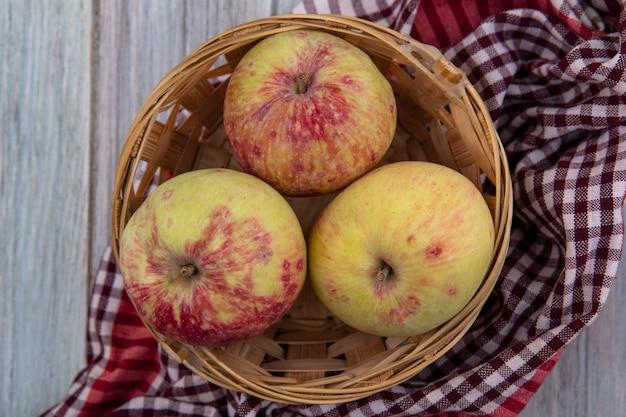 Vue de dessus de pommes juteuses fraîches sur un seau sur un tissu vérifié sur fond gris