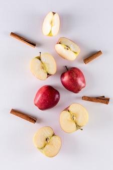 Vue de dessus des pommes à moitié coupées avec de la cannelle sur blanc vertical