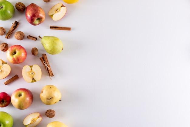 Vue de dessus des pommes à moitié coupées avec de la cannelle et de la poire avec copie espace à droite sur blanc