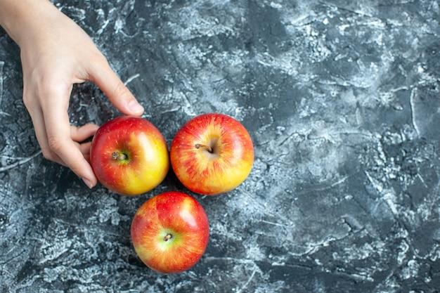 Vue de dessus des pommes mûres main féminine sur fond gris avec lieu de copie