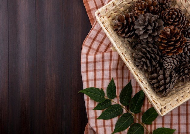 Vue de dessus des pommes de pin sèches sur panier avec feuille sur nappe à carreaux et bois