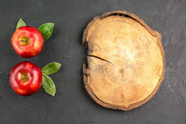 Vue de dessus pommes rouges fraîches fruits moelleux sur une table sombre fruits rouges frais mûrs