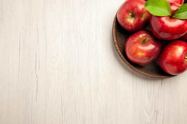 Vue de dessus pommes rouges fraîches fruits mûrs et moelleux sur un bureau blanc couleur des fruits arbre plante fraîche rouge