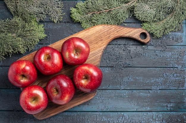Vue de dessus des pommes rouges fraîches des fruits mûrs moelleux sur un bureau bleu foncé couleur des fruits des plantes fraîches de nombreuses vitamines rouges
