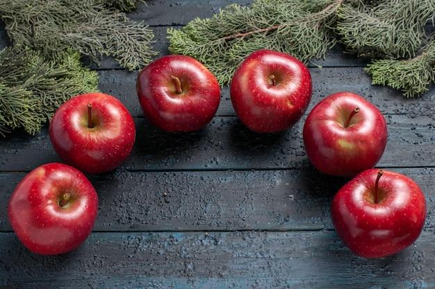 Vue de dessus des pommes rouges fraîches des fruits mûrs moelleux sur un bureau bleu foncé couleur des fruits des plantes rondes fraîches de nombreuses vitamines rouges