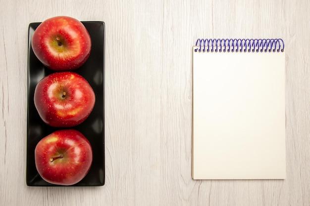 Vue de dessus pommes rouges moelleuses fruits frais à l'intérieur d'une casserole noire sur un bureau blanc fruits moelleux mûrs couleur rouge frais