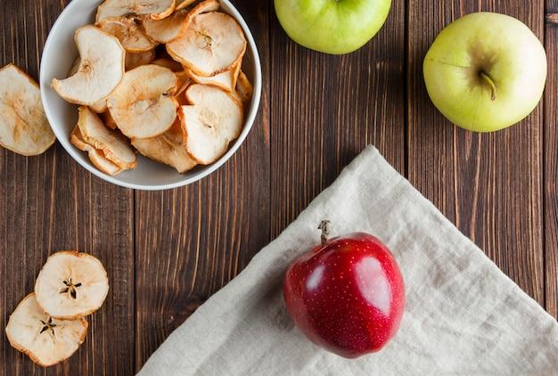 Vue de dessus des pommes séchées dans un bol avec des pommes fraîches sur un tissu et un fond en bois. horizontal