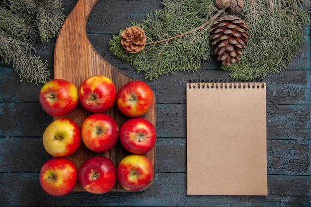 Vue de dessus des pommes sur une table pommes jaune-rouge sur une planche à découper en bois sur une surface grise et un ordinateur portable entre les branches des arbres