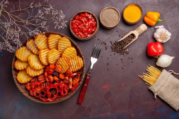 Vue de dessus des pommes de terre au four avec des légumes cuits et des assaisonnements sur un bureau sombre
