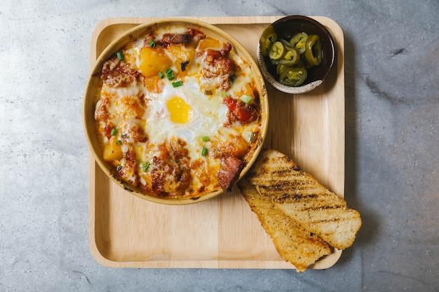 Vue de dessus des pommes de terre au fromage avec bacon croustillant et oeuf au plat.