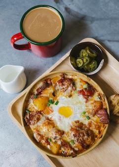 Vue de dessus des pommes de terre au fromage avec bacon croustillant et œuf au plat.