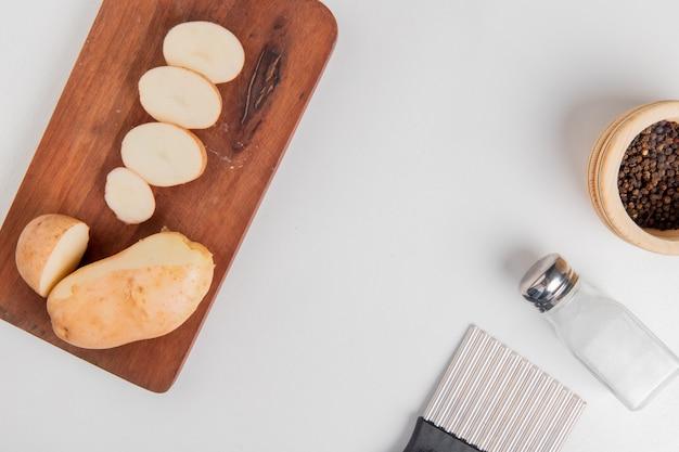 Vue de dessus des pommes de terre coupées et tranchées sur une planche à découper avec du sel, du poivre noir et un coupe-chips sur une surface blanche