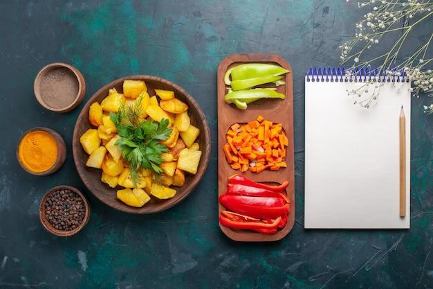 Vue de dessus des pommes de terre cuites avec des légumes verts avec des assaisonnements et des poivrons en tranches sur une surface bleu foncé