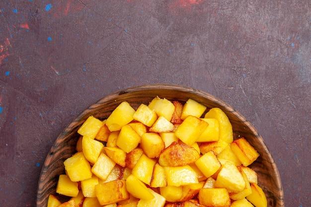 Vue de dessus des pommes de terre cuites en tranches à l'intérieur de la plaque brune sur le bureau sombre