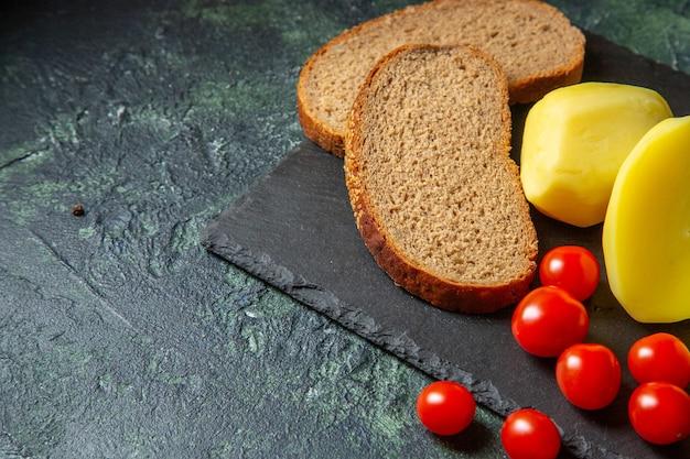 Vue de dessus des pommes de terre fraîches coupées pelées et des tranches de pain diététique tomates paquet vert sur une planche à découper en bois sur le côté gauche sur fond de couleurs de mélange noir vert avec espace libre