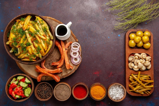 Vue de dessus des pommes de terre frites avec des assaisonnements et différents légumes sur le bureau sombre