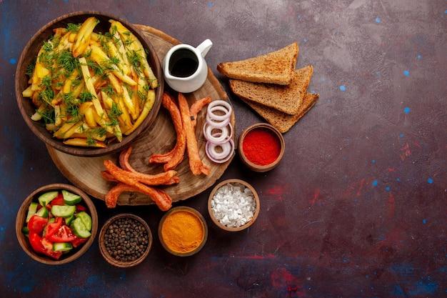 Vue de dessus des pommes de terre frites avec des assaisonnements, des miches de pain et différents légumes sur le bureau sombre