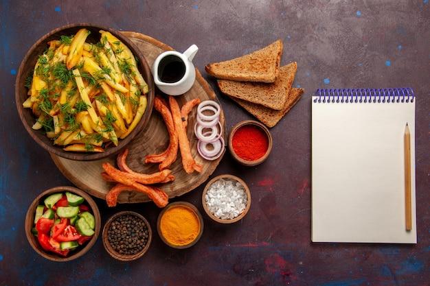 Vue de dessus des pommes de terre frites avec des assaisonnements, des miches de pain et différents légumes sur la surface sombre