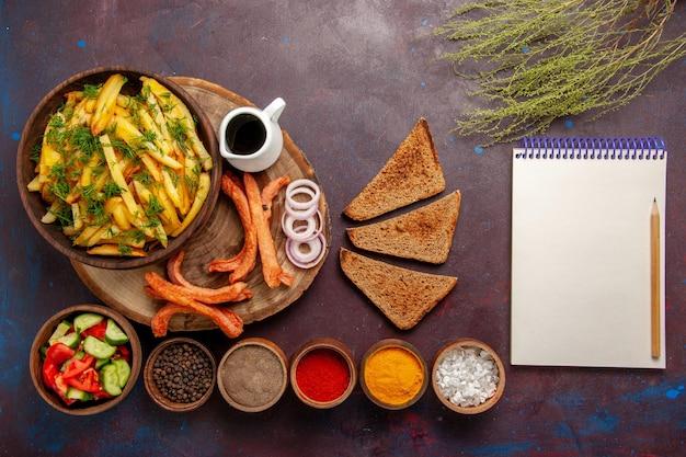 Vue de dessus des pommes de terre frites avec du pain d'assaisonnement et différents légumes sur le bureau sombre