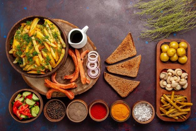 Vue de dessus des pommes de terre frites avec du pain d'assaisonnement et différents légumes sur la surface sombre